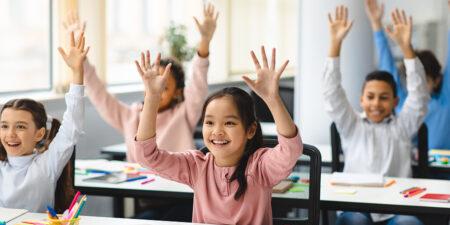 Barn som lyfter händerna i ett klassrum.