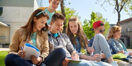 Ungdomar sitter på en gräsmatta.
