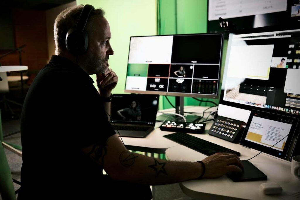 Roland Träskelin sitter framför ett bord med sändningsutrustning; skärmar och datorer.