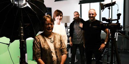 Siv Björklund, Carina Österåker, Stefan Westergård och Roland Träskelin står i en studio. I förgrunden till vänster syns en stor fotolampa och en greenscreen.