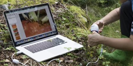 Dator kopplad till ett mikroskop i skogen.