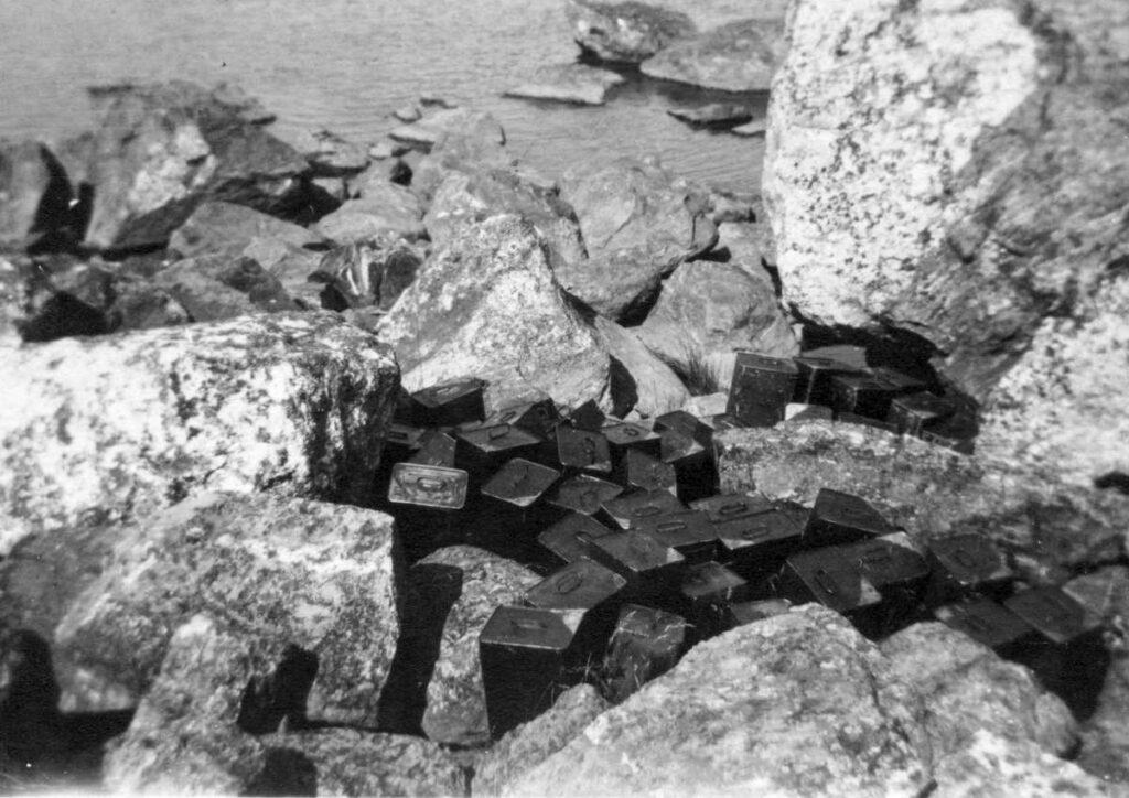 En gammal svartvit bild på stora stenar vid havsstranden, bland stenarna skymtar svarta kanistrar.