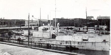 En gammla svartvit bild på ett fartyg vid kaj.