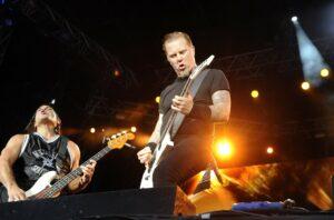 Metallicas basist och sångare/gitarrist fotograferade på scenen med stark orange strålkastare i bakgrunden.