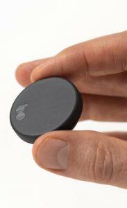 Närbild av en hand som håller i en rund, svart sensor