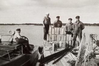 En gammal svartvit bild där fyra män sår på en brygga, framför sig har den en stor mängd gammaltida spritkanistrar.