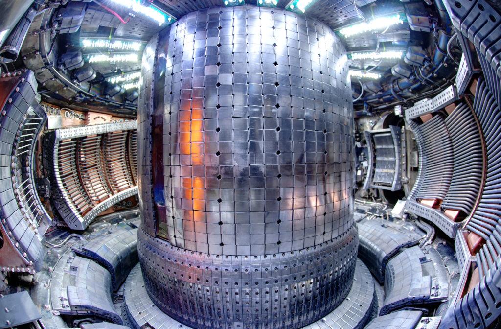 Fusionsreaktorns innandöme. En cylinder i mitten omgiven av runda väggar, allt i olika nyanser och kombinationer av metall, plattor, rör och lampor.