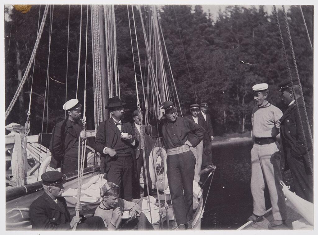 En gammal svartvit bild där en grupp unga män står på ett segelbåtsdäck.