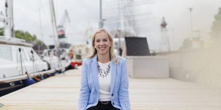 En leende Sandra Bergqvist sitter på en brygga.