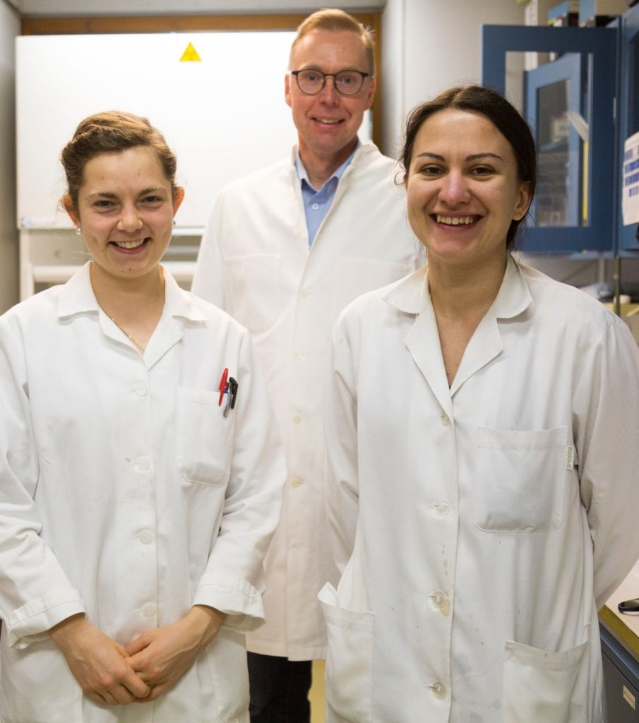 Portrait of Emily Kemp, Johan Bobacka and Zhanna Boeva standing i a laboratory dressed in lab coats.