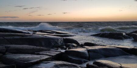 En stormig havsvy i solnedgång.