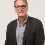 Porträttbild på Fredrik Nilsson, en man med glasögon i skjorta och kavaj.