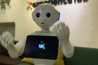 Roboten Pepper gestikulerar med armarna.