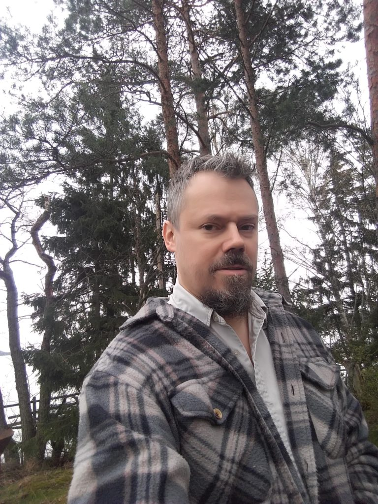 Porträttfoto på Mats Nyholm. Träd i bakgrunden.