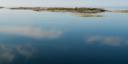 Ett spegelblankt hav en solskensdag. I horisonten ses små öar.