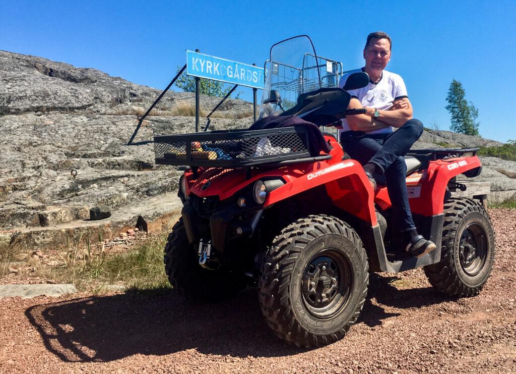 Markus Nordberg sitter på en fyrhjuling. I bakgrunden en skylt där det står Kyrkogårdsö.