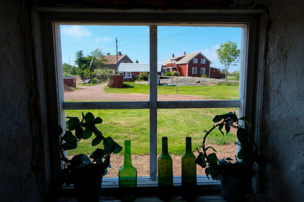 Foto taget inifrån, genom ett fönster, utanför ser man ett stort rött hus en vacker sommardag.