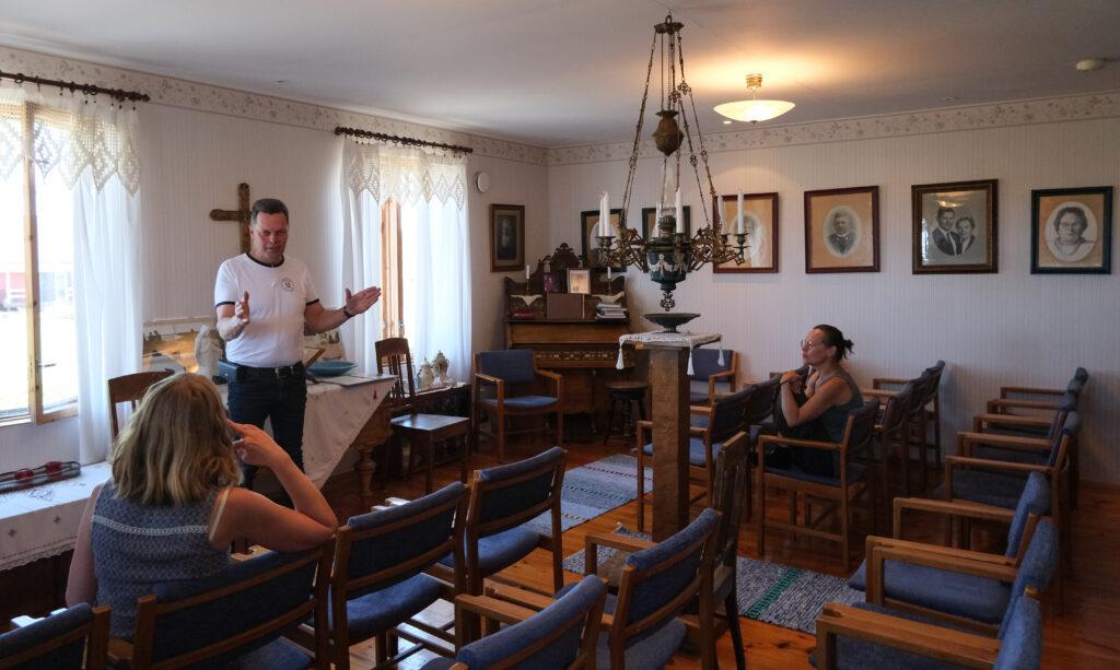 Markus Nordberg står i ett stort rum och pratar framför två åhörare,