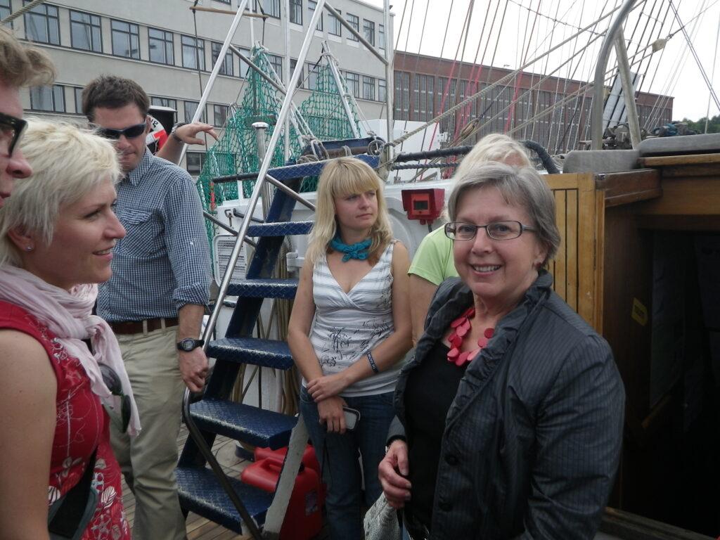 Tre glada kvinnor språkas på ett fartygsdäck.