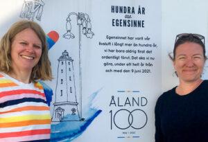 Två glada kvinnor vid en reklam för Ålands 100-årsjubileum, där det står Hundra år av egensinne.