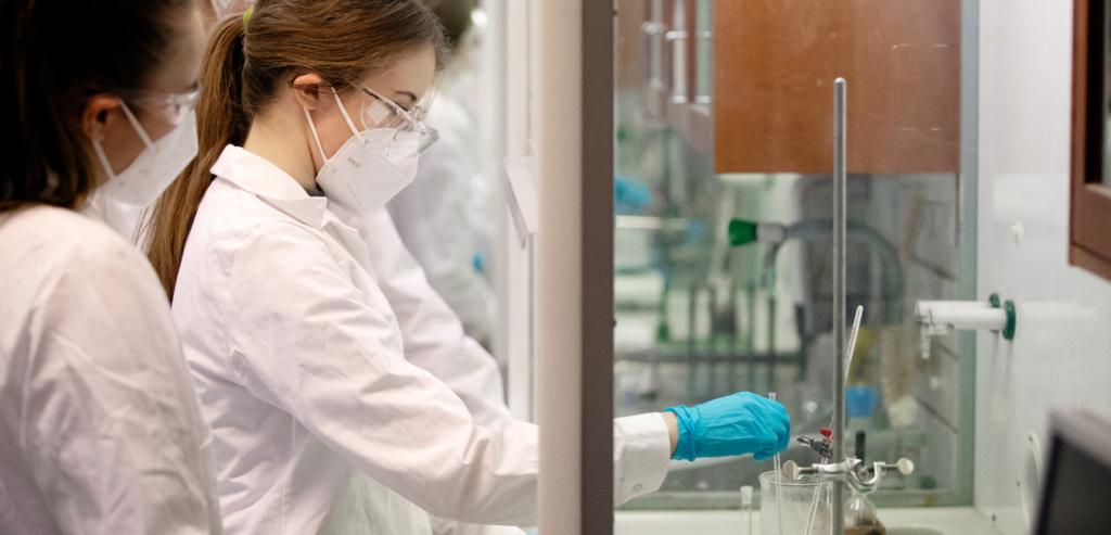 Kvinna med ansiktsmask som utför ett experiment i ett laboratorium.
