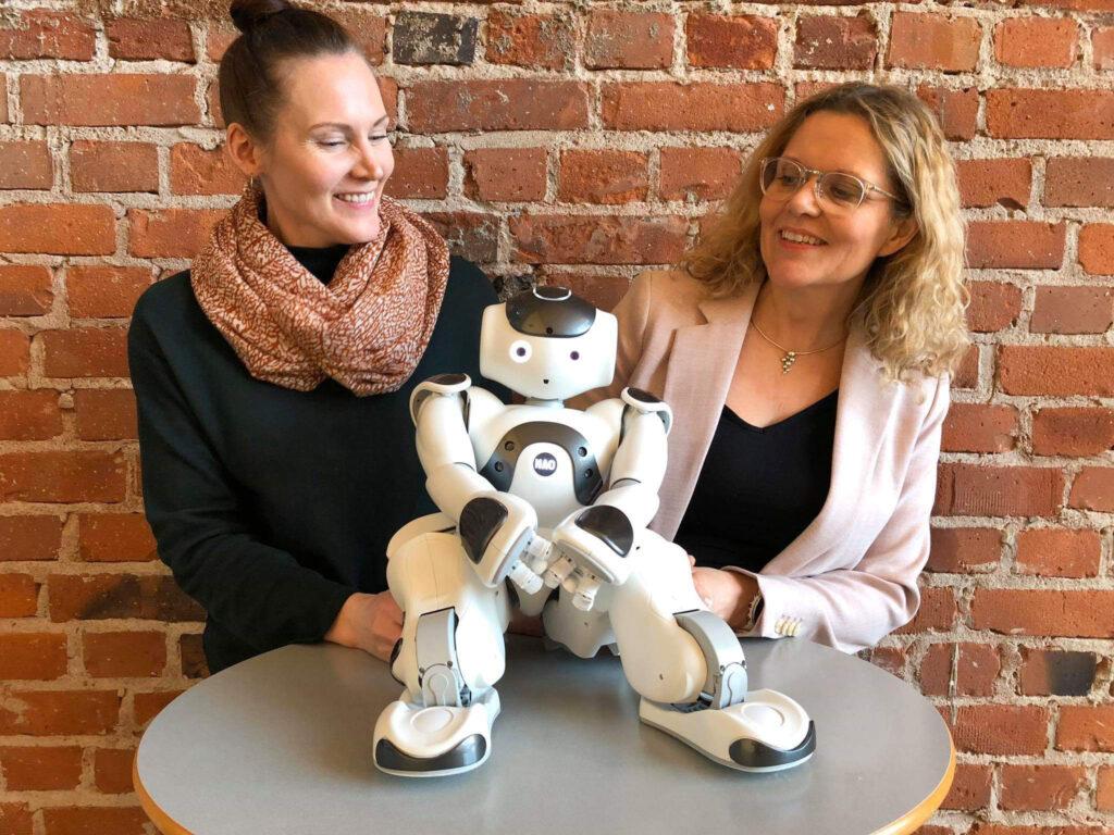 Två glada kvinnor tillsammans med en liten humanoid robot.