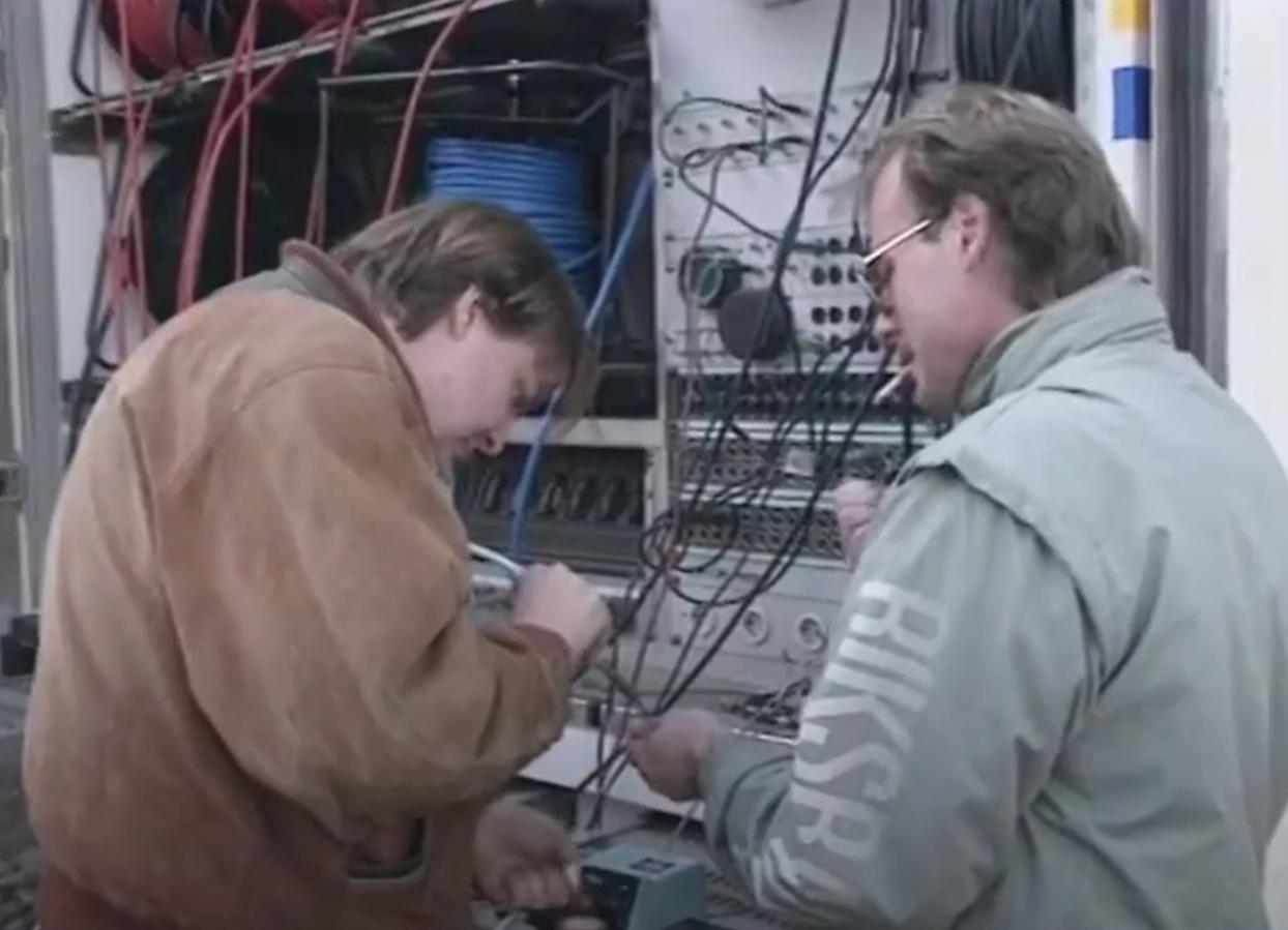 Två män vända mot ett mixerbord, ena mannen har en tobak i mungipan.