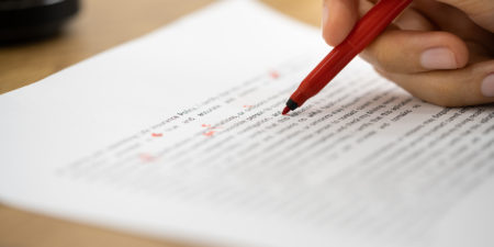 En röd penna markerar på ett papper med text.