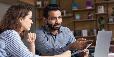 En yngre och en äldre person, typ student, lärare, diskuterar en gemensam text.