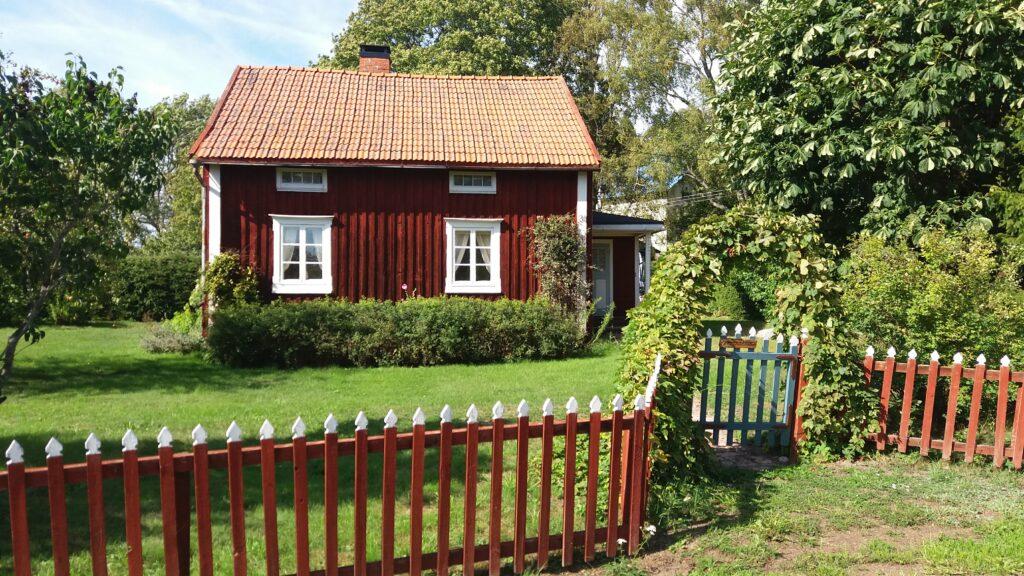 En liten röd stuga med vita knutar, bakom ett rött staket.