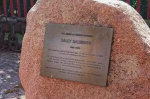 En sten i röd granit med en plakett på.